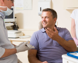 photo of male patient conversing with dentist